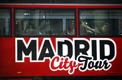 Tourism stop: A Madrid tour bus travels through the city with only a few passengers onboard.