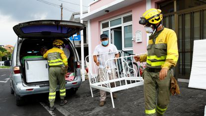 Members of the Forest Fire Reinforcement Brigades (BRIF) help a resident to carry furniture in Todoque on Monday.