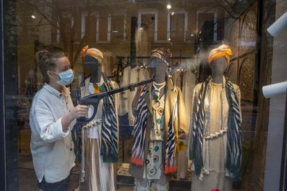 Disinfecting a display window at a fashion boutique in San Sebastián.