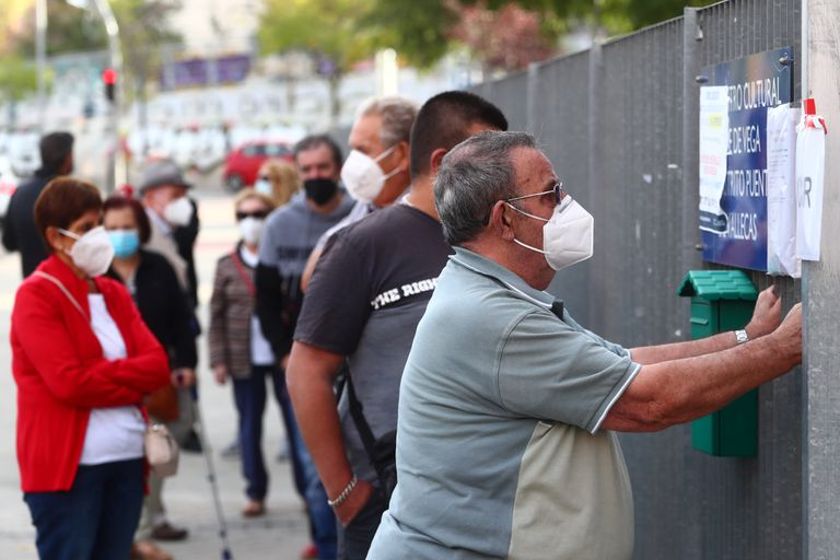 People wait in line outside a cultural centre to take a coronavirus antigen test in the Madrid neighborhood of Vallecas.