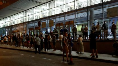 People wait in line to get vaccinated at the Wizink Center arena in Madrid.