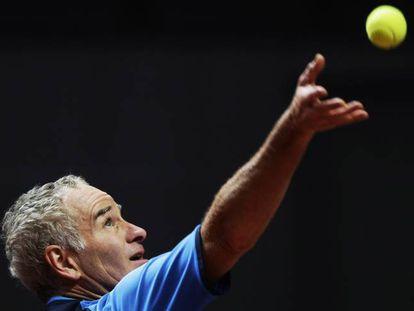 John McEnroe serves during an exhibition match.