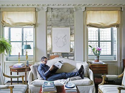 """James Costos, in his New York residence underneath an Ellsworth Kelly work titled 'Pear.' """"I love to lie on the sofa with my feet up,"""" he admits. He is wearing a GIORGIO ARMANI shirt, APC jeans, a LOUIS VUITTON belt and GIVENCHY shoes."""