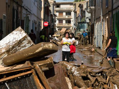 Residents remove destroyed furniture from their houses in Sant Llorenc.