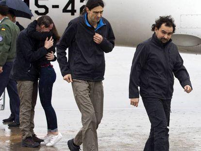 Ángel Sastre (right), José Manuel López (center) and Antonio Pampliega (hugging a relative) arriving in Madrid on Sunday.