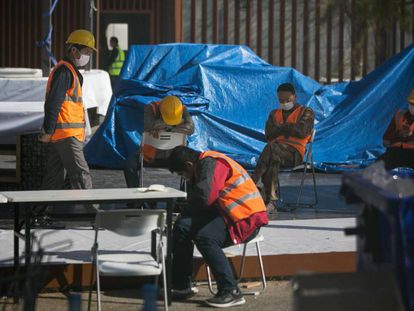 Workers, some with face masks, after the cancellation of the Mobile World Congress.