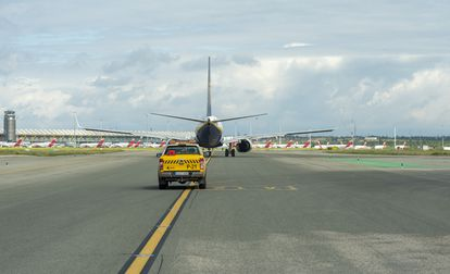A vehicle guides an aircraft on a runway at Madrid-Barajas airport.