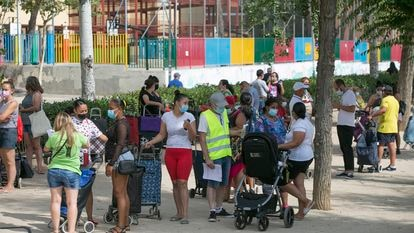 Dozens of people wait in line to collect food donations in Aluche.