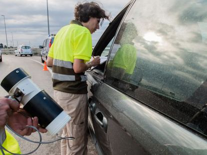 Researchers from the Mosquito Control Center in Baix Llobregat (Catalonia) look for tiger mosquitoes at a traffic stop.