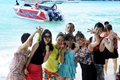 A group of Chinese tourists enjoying a day on the beach in Thailand.