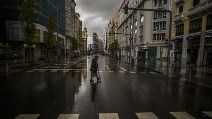 A woman crosses a deserted Gran Vía in Madrid, on March 23, 2020 during the state of alarm in Spain.