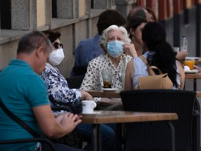 Patrons with masks sit at a street café in Seville, southern Spain on Wednesday