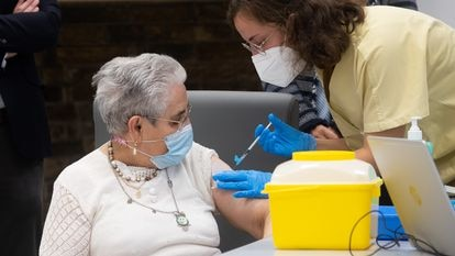 A health worker administers a third vaccine dose to a nursing home resident.
