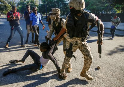 Demonstrators are detained by police during the protests in Haiti.