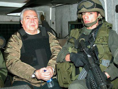 Police officers escort the drug kingpin Gilberto Rodríguez Orejuela in 2004.