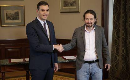 Caretaker prime minister Pedro Sánchez shakes hands with Unidas Podemos leader Pablo Iglesias.