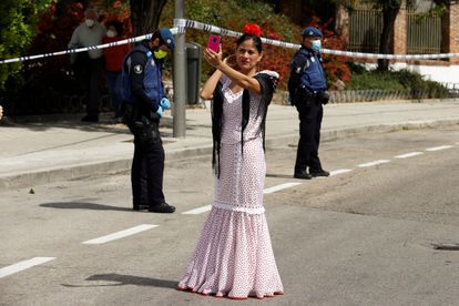 A woman dressed in traditional 'chulapa' dress observes the Day of San Isidro, the patron saint of Madrid, under security measures due to the coronavirus.