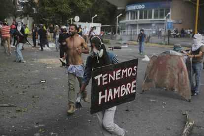 """We're hungry"" reads a placard carried by a protester Monday in Caracas."
