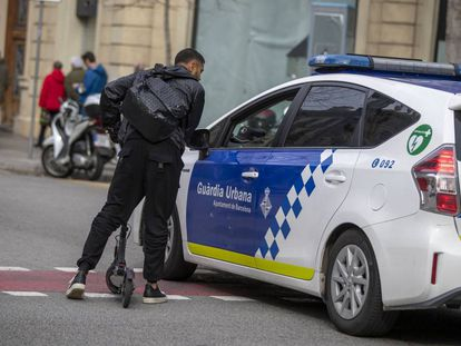 Local police issue a warning to a man on a scooter.