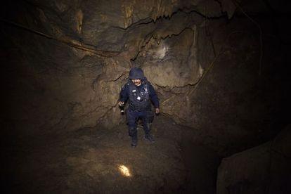 A policeman searches the cave where La Tuta hid out.
