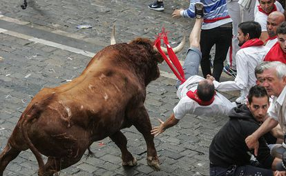 A runner is flipped up into the air during Day 4 of the Running of the Bulls.