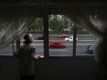 Naime Sajit looks out of her home onto the Extremadura highway in Madrid.