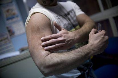 Álex, a transgender man, applies a testosterone gel.