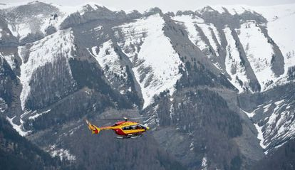A French Civil Protection helicopter flies over the crash site area.