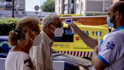 A health worker checks the temperature of residents in Villaverde, Madrid.