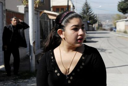 Leonarda Dibrani, the 15-year-old schoolgirl whose deportation from France sparked a huge outcry, speaks to the media as her father Resat talks on his cellphone outside their temporary home in Mitrovica.