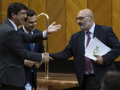 The premier of Andalusia, Juan Manuel Moreno Bonilla (c), and the deputy permier Juan Marín (l), shake hands with Vox regional spokesperson Alejandro Hernández.