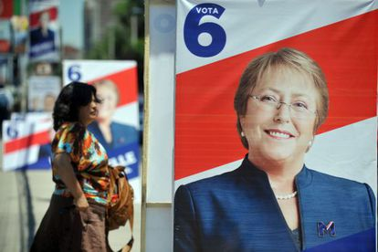 A woman walks past a campaign poster for Michelle Bachelet in Santiago.