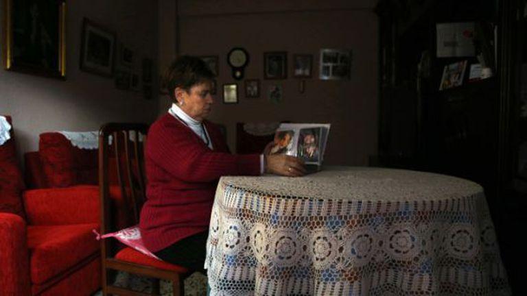 Benedicta García looks at photos of her daughter Pilar at home in Logroño.