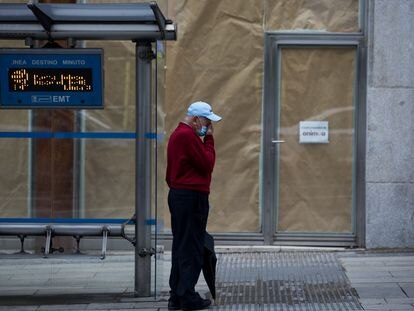 A man waits at a bus stop on Gran Vía avenue in Madrid.