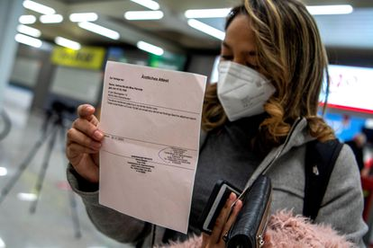A passenger arriving in Palma de Mallorca on a flight from Germany shows her negative PCR test.