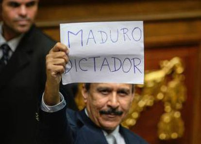 """A Venezuelan opposition deputy holds up a sing reading """" Maduro dictator"""" during an extraordinary session of the National Assembly on Sunday."""