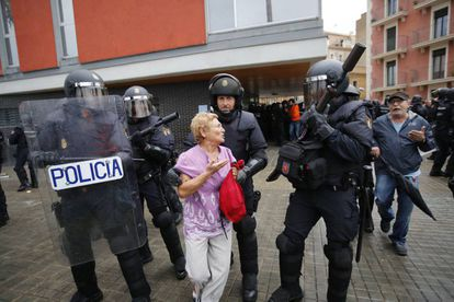 Riot police tell a woman not to enter a polling station at the Mediterránea de la Barceloneta school in Barcelona.