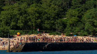 Groups of youngsters line up to jump off the jetty at Magdalena beach in Santander.