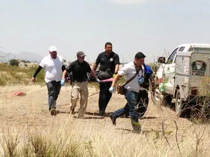 Authorities carry the body of six-year-old Christopher who was killed on the outskirts of Chihuahua.