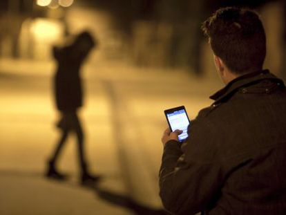 A man checks his cellphone as a young woman walks by.