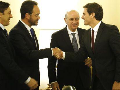 Ciudadanos leader Albert RIvera greets Socialist spokesman Antonio Hernando next to his PP counterpart Rafael Hernando (far left) and Interior Minister Jorge Fernández Díaz.