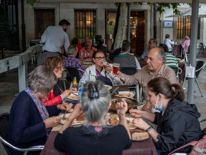 A group of people dining at a sidewalk café in Ourense.
