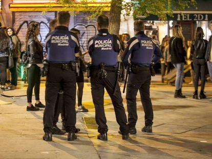 Police break up people drinking on the street in Madrid.