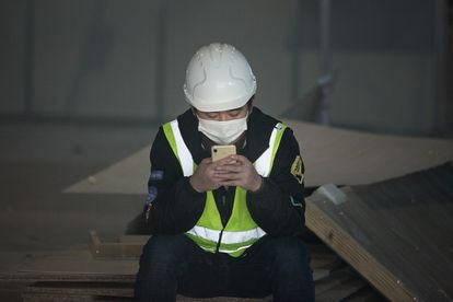 A worker looks at his cellphone in Barcelona, last February.