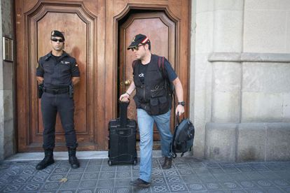 Civil Guard officers walk out of Catdem and Fòrum Barcelona after searching the premises in August.