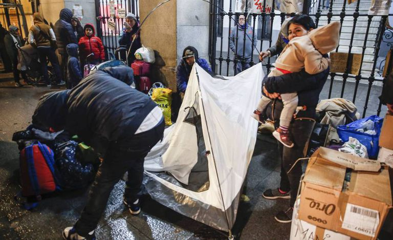 Asylum seekers lining up outside a social services building in Madrid.