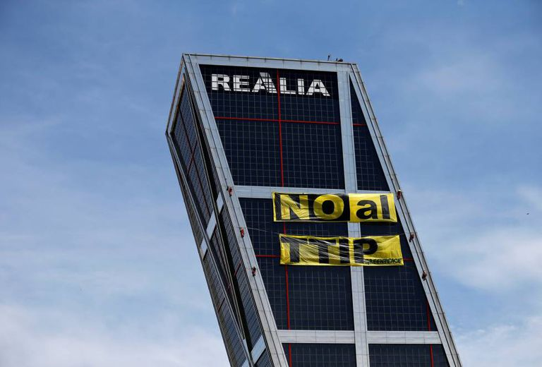 Greenpeace activists unfurling an anti-TTIP banner on a Madrid tower.