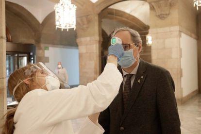 Catalan premier Quim Torra undergoing a temperature check inside the regional parliament on Friday.