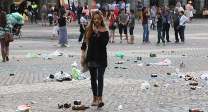 A passer-by navigates the beer bottles and other trash left behind by soccer fans in Madrid's Plaza Mayor.