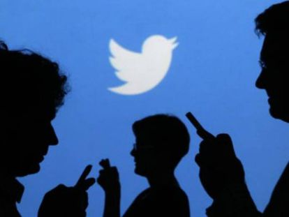 Smartphone users in front of a Twitter logo.